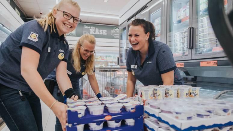 Lehrlinge beim Verräumen von Milchprodukten