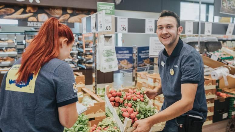 Lehrlinge beim Aufbauen von Obst und Gemüse