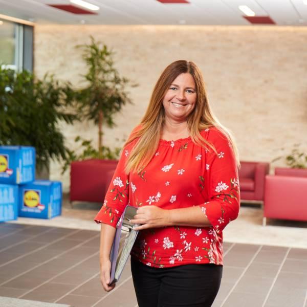Eva steht im Eingangbereich mit einer Mappe